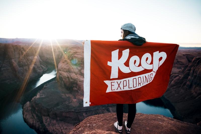 Dziewczyna zflagą Keep Exploring naszczycie Fot. Justin Luebke/Unsplash