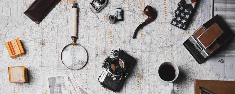 Mapa, lupa, aparaty, rolki filmowe, buty, notes Photo by ian dooley on Unsplash