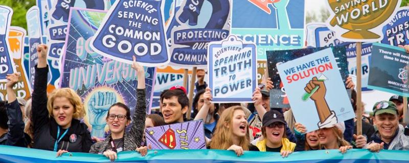 Tłum z hasłami promującymi naukę Photo by Vlad Tchompalov on Unsplash