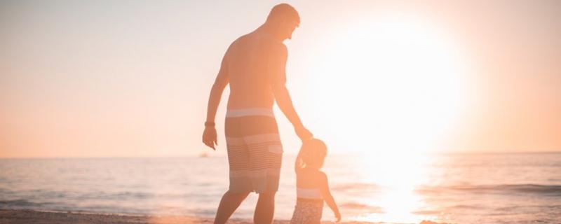 Dorosły prowadzący dziecko na plaży Photo by Derek Thomson on Unsplash