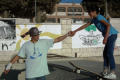 A. Szostek uczy jazdy na deskorolce dziewczynkę w Palestynie.